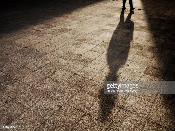 shadow of a walking person - striding stock pictures, royalty-free photos & images