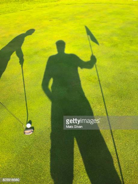 shadow of a woman and a caddy putting on golf course - golfbaan green stockfoto's en -beelden
