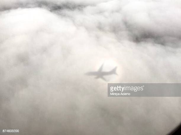 Shadow of airplane on cast on the white clouds