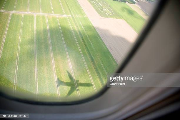 Shadow of airplane on field, aerial view from window