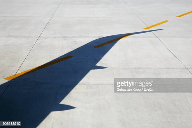 shadow of airplane on runway - airport runway stock pictures, royalty-free photos & images
