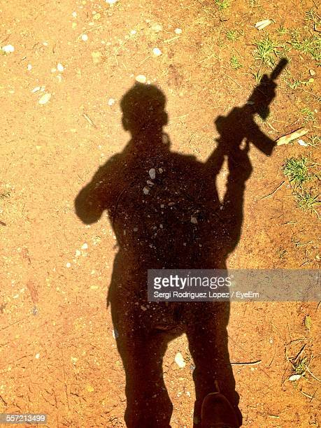 shadow of army soldier with machine gun casting on ground - violence stock photos and pictures