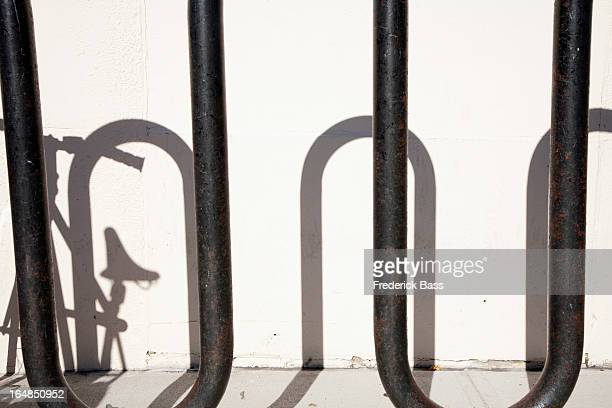 Shadow of bike parked in bicycle stand