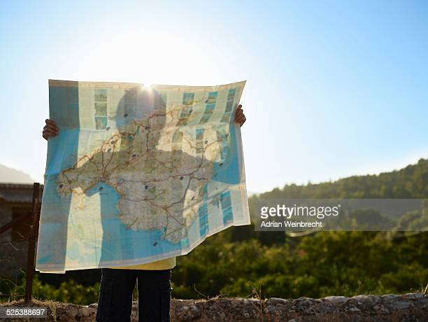 shadow of boy holding up a map, majorca, spain - karte navigationsinstrument stock-fotos und bilder