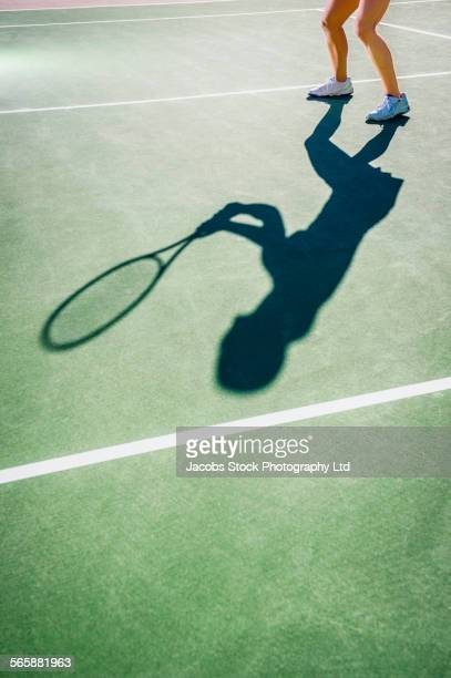 Shadow of Caucasian woman playing tennis