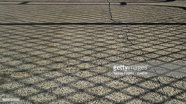 shadow of chainlink fence on street - chainlink fence stock pictures, royalty-free photos & images