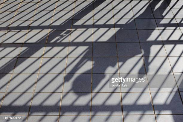 shadow of child behind bars - torture stock pictures, royalty-free photos & images
