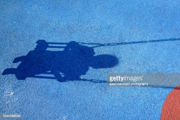Shadow of child on playground swing