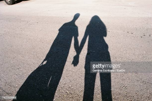 Shadow Of Couple Holding Hands At Street