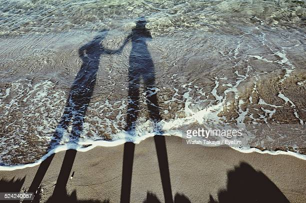 Shadow of Couple Holding Hands On Beach