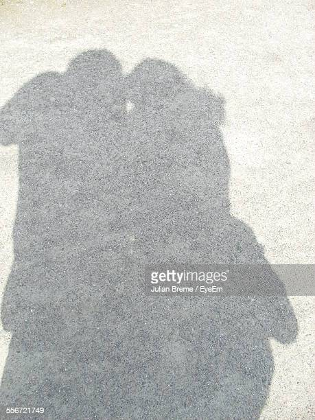 Shadow Of Couple Kissing On Road