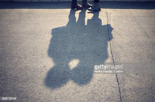 shadow of couple on concrete driveway - leg kissing stock photos and pictures