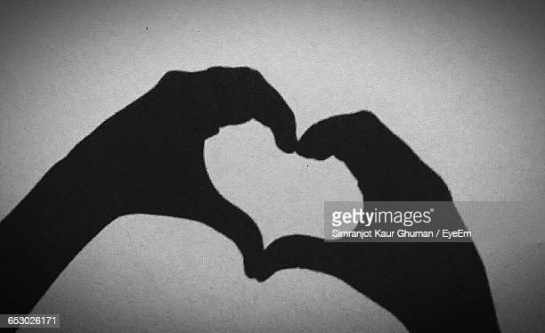Shadow Of Cropped Hands Making Heart Shape On Wall