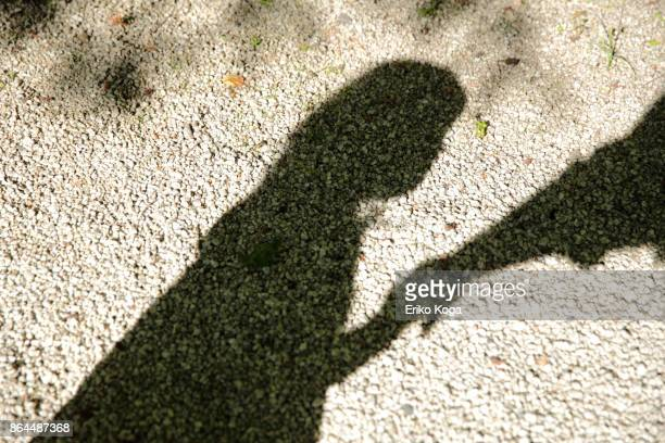 Shadow of daughter and father holding hands