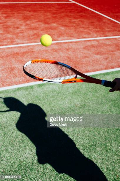 shadow of female tennis player serving ball . - tennis player stock pictures, royalty-free photos & images