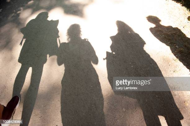 Shadow of four women on a sunny day