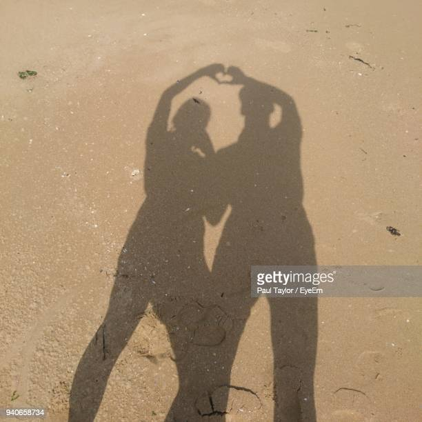 Shadow Of Friends On Sand At Beach