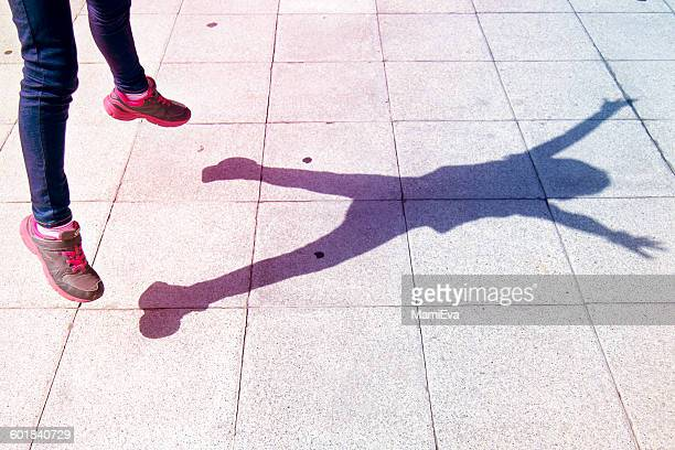 shadow of girl jumping in air - ombra in primo piano foto e immagini stock