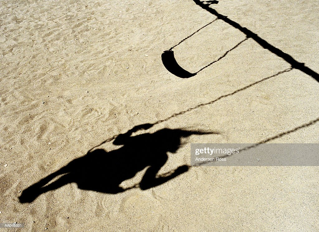 Shadow of girl on swing : Stock Photo
