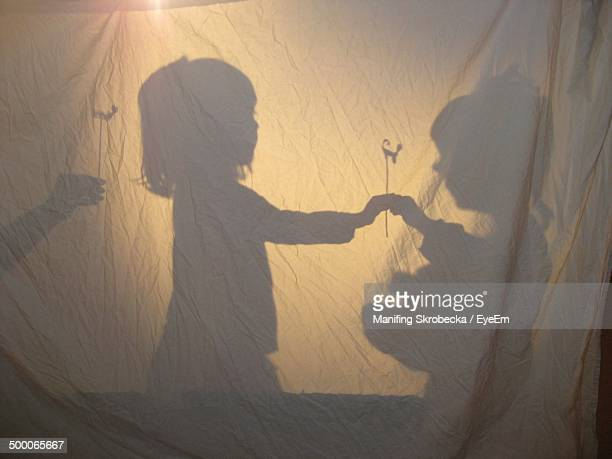 shadow of girls playing behind curtain at night - storytelling stock pictures, royalty-free photos & images