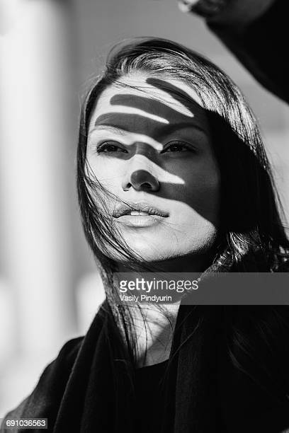 Shadow of hand on thoughtful womans face during sunny day
