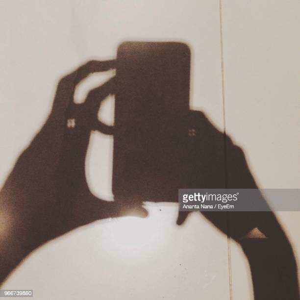 Shadow Of Hands Holding Mobile Phone
