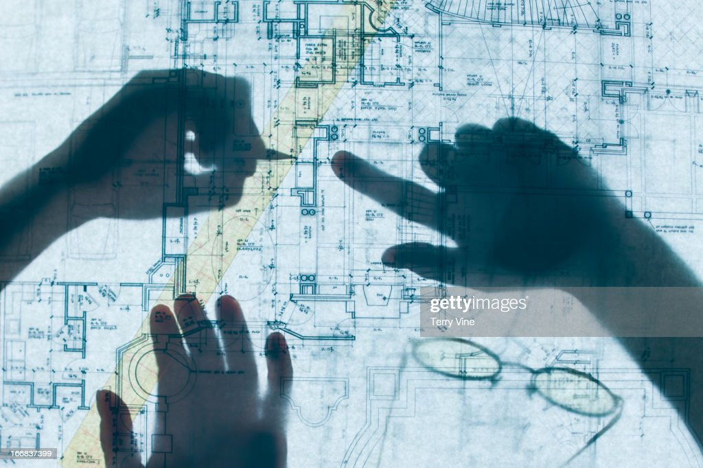 Shadow of hands on blueprints : Stock Photo