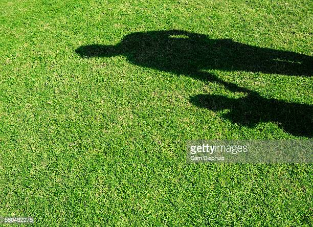 Shadow of Hispanic father and son on grass lawn