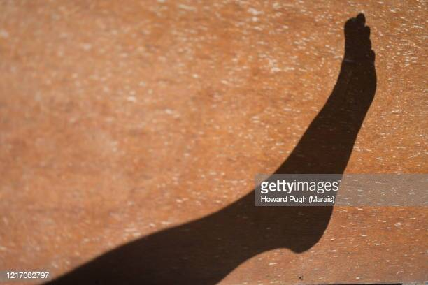 a shadow of human limbs - howard pugh stock pictures, royalty-free photos & images