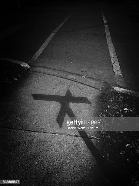 shadow of information sign on empty footpath at night - rachel wolfe stock pictures, royalty-free photos & images