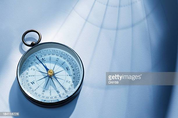 shadow of latitude and longitude lines cast onto a compass - compass stock pictures, royalty-free photos & images