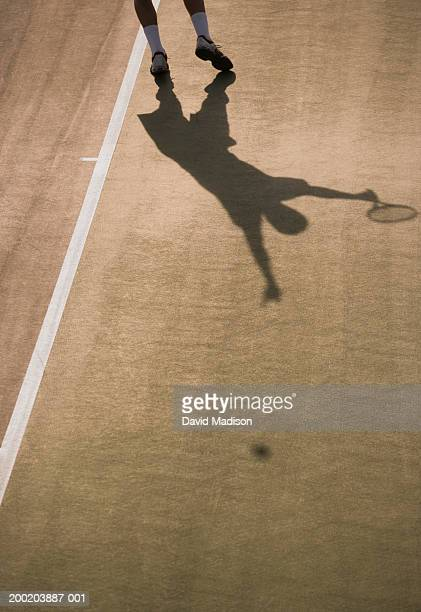 Shadow of male tennis player serving ball, low section view of player.