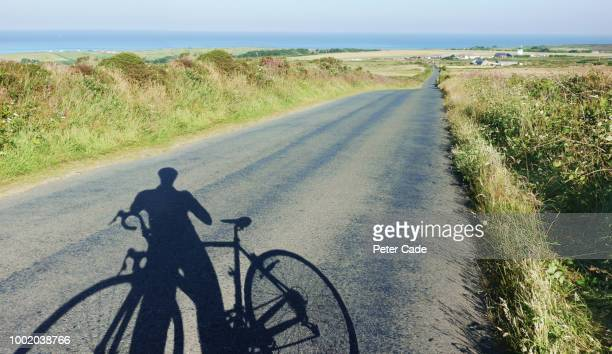 Shadow of man and bike on coastal road