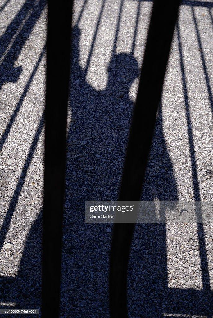 Shadow of man behind bars : Stock Photo
