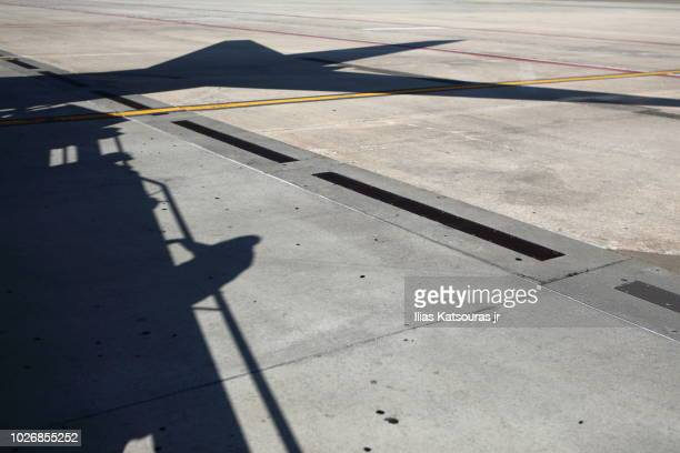shadow of man boarding airplane - airport tarmac stock pictures, royalty-free photos & images