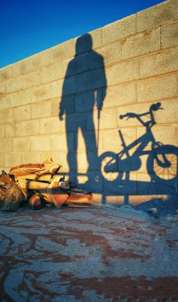 Shadow Of Man On Bicycle Against Wall