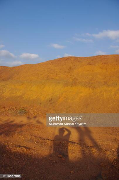 shadow of man on desert land against sky - muhamad nasrun stock pictures, royalty-free photos & images
