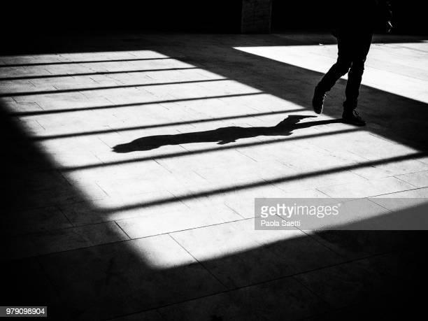 shadow of man on pavement - 背景に人 ストックフォトと画像