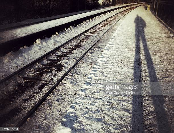 Shadow Of Man On Snowcapped Railroad Station Platform During Sunny Day