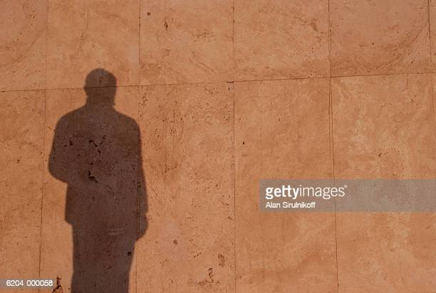 shadow of man on wall - sirulnikoff stock photos and pictures