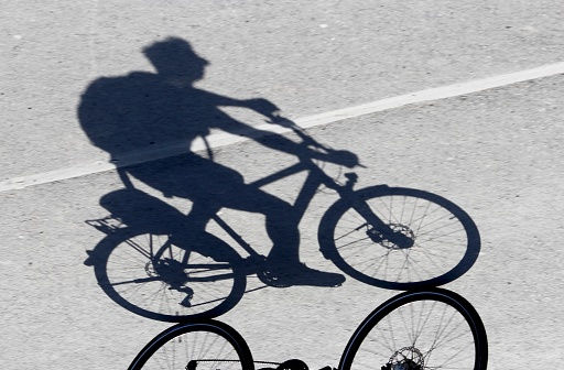 Shadow Of Man Riding Bicycle On Road - gettyimageskorea