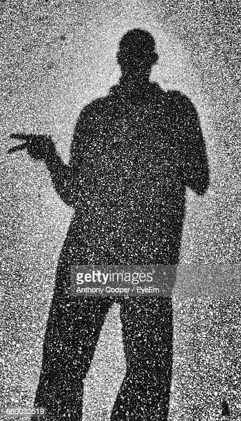 Shadow Of Man Showing Victory Sign On Road
