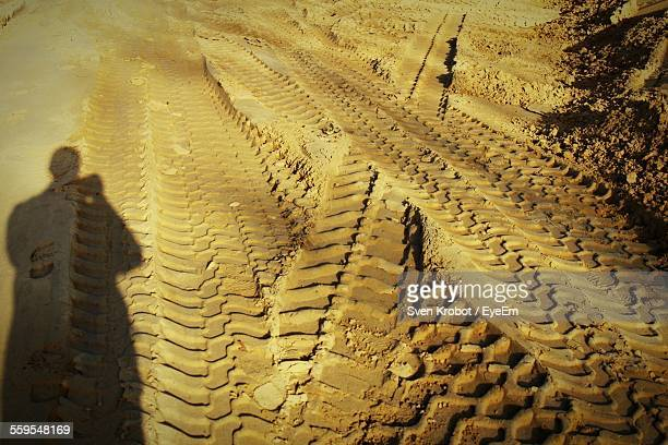 Shadow Of Man Standing Against Tire Tracks On Muddy Road