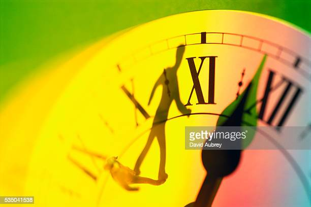 Shadow of Man Walking on Clock About to Strike Midnight