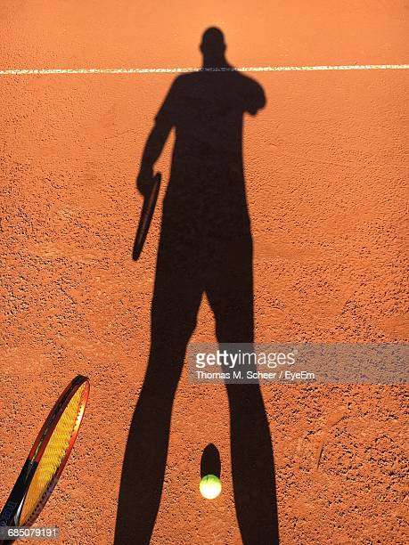 Shadow Of Man With Tennis Racket And Ball On Clay Court