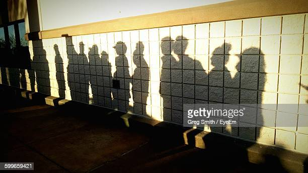shadow of men and women standing in queue on wall - lining up stock pictures, royalty-free photos & images