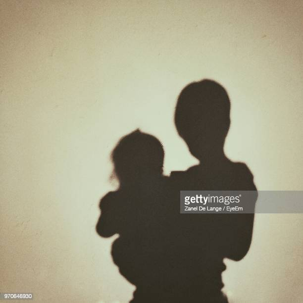 shadow of mother and daughter on wall - schaduw stockfoto's en -beelden