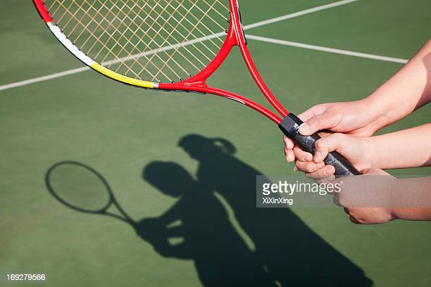 Shadow of mother and daughter playing tennis