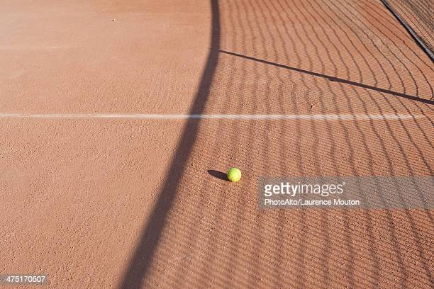 Shadow of net in tennis court over tennis ball