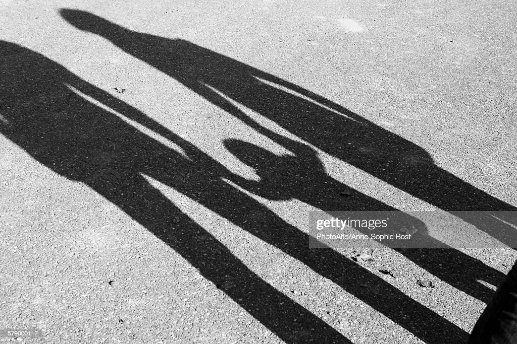 Shadow of parents and child holding hands : Stock Photo